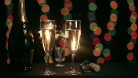 Two glasses of champagne on the background of burning sparkler. Background lights bokeh. Closeup stock video footage