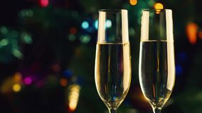 Two glasses of champagne on the background of the christmas tree. The celebration of christmas and new year stock video footage