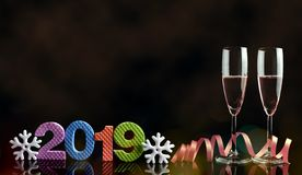 Two glasses with champagne and number 2019 on black background. royalty free stock images