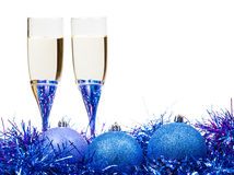 Two glasses of champagne at blue and violet tinsel Royalty Free Stock Image