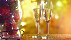 Two glasses of champagne with bokeh lights in the. Two glasses of champagne with golden lights in the background stock video