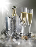 Two glasses of champagne with bottle in cooler on a silver background, selective focus stock image