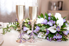 Two glasses of champagne and a bouquet of lilac freesias and white callas. Stock Photos