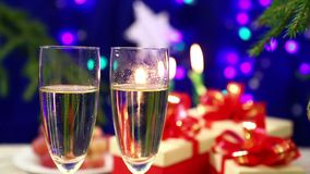 Two glasses with champagne with bubbles in the foreground on the table with gifts on the New Year`s background with herlands. Shot with dolly from right to stock footage