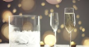 Festive bubbles in a glass of sparkling wine. Two glasses of champagne with bubbles and an ice bucket on the background of festive lights and gray wall stock footage