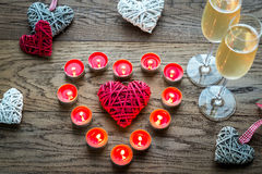 Two glasses of champagne with burning candles and cane hearts Royalty Free Stock Images