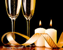 Two glasses with champagne and candles Stock Photos
