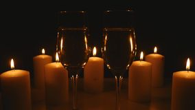 Two glasses of champagne with candles on black background.  stock video