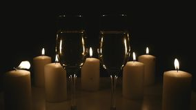 Two glasses of champagne with candles on black background.  stock video footage