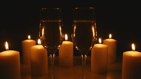 Two glasses of champagne with candles on black background.  stock footage