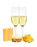 Two glasses of champagne, candles and yellow rose isolated. On white background Stock Photos