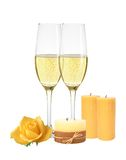 Two glasses of champagne, candles and yellow rose isolated on wh Royalty Free Stock Photos