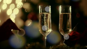 Two glasses with champagne on Christmas Eve. Christmas decoration and illumination on the background stock video
