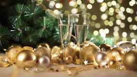 Two glasses of champagne with christmas present and christmas balls stock footage