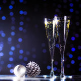 Two glasses of champagne with Christmas toys. Festive lights bok Stock Image