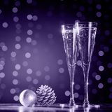 Two glasses of champagne with Christmas toys. Festive lights bokeh background. Ultra violet tone, color of the year 2018. Two glasses of champagne with Christmas stock images
