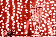 Two glasses of champagne with Christmas toys. Festive lights bokeh background. Coral accent - color of the year 2019. Two glasses of champagne with Christmas stock photos