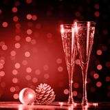Two glasses of champagne with Christmas toys. Festive lights bokeh background. Ultra violet tone, color of the year 2018 . Living. Two glasses of champagne with royalty free stock photos