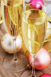 Two glasses with champagne and Christmas tree decorations on the Stock Images