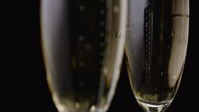 Two glasses with champagne closeup of bubbles rise up. Black background. Two glasses with champagne close up, bubbles rise up the glass sparkling wine. Black stock video