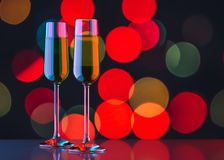 Two glasses of champagne on bokeh background. Two glasses of champagne on colorful bokeh background. Festive attribute of christmas or other celebration Royalty Free Stock Photos