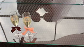 Two glasses of champagne with colorful ribbons on the table. Reflection of the wedding couple on the glass. Two glasses of champagne with colorful ribbons on stock video