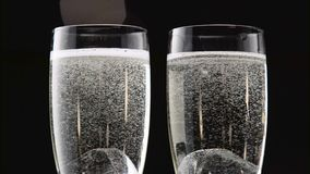 Two flutes of champagne with ice on the bottom. Bokeh blinking black background. Close up. Two glasses of champagne cooled with pieces of ice plunging to the stock video footage
