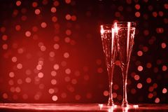 Two glasses of champagne on dark bokeh background. Ultra violet tone, color of the year 2018 . Living coral theme - color of the. Two glasses of champagne on royalty free stock photo