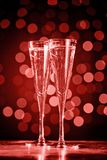 Two glasses of champagne on dark bokeh background. Ultra violet tone, color of the year 2018 . Living coral theme - color of the. Two glasses of champagne on stock image