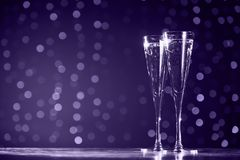 Two glasses of champagne on dark bokeh background. Ultra violet royalty free stock photos