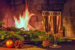 Two glasses of champagne, decorations, Christmas tree branches and a candle on a wooden table in front of a burning fireplace royalty free stock image