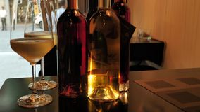 Two glasses of champagne and different colors bottles of wine exhibition in the wine bar space in Spain. Two glasses of champagne and different colors bottles stock video footage