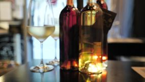 Two glasses of champagne and different colors bottles of wine exhibition in the wine bar space in Spain. Barcelona. Lighted street view background 4 k stock footage