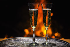Two glasses of champagne with flame on background. Two glasses of champagne with campfire on background Royalty Free Stock Photos