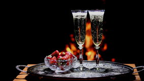 Two glasses of champagne with flame on background. Two glasses of champagne with campfire on background stock video