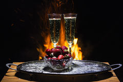 Two glasses of champagne with flame on background. Two glasses of champagne and strawberry with flame on background Royalty Free Stock Image