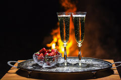 Two glasses of champagne with flame on background. Two glasses of champagne and strawberrywith flame on background Stock Image