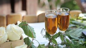Two glasses of champagne and flowers on the table. Two glasses of champagne and flowers on the table, close-up stock footage