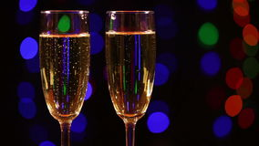 Two glasses with champagne. In front of black background with colorful flashing lights stock video footage