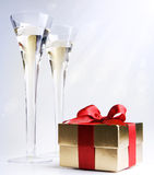 Two glasses of champagne and a gift royalty free stock image