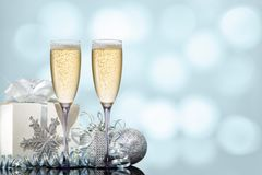 Two glasses of champagne with a gift and Christmas toys on a turquoise background. Two glasses of champagne with a gift and Christmas toys on a festive turquoise stock photos
