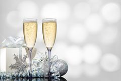 Two glasses of champagne with a gift and Christmas toys. On a festive background royalty free stock image