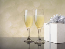 Two glasses of champagne with a gift on a festive background.  Royalty Free Stock Photos