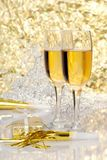 Two glasses champagne with gift and horns. On a gold sparkle background Royalty Free Stock Photography