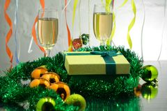 Two glasses of champagne with a gingerbread house New Year`s decorations on a New Year`s table on a background of a Christmas tr Royalty Free Stock Photos