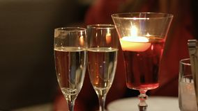 Two glasses with champagne and glass with burning candle on table. Camera moves from left to right. Two glasses with champagne and glass with burning candle stock video