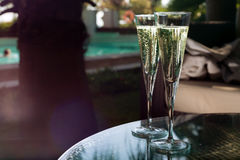 Two glasses of champagne. On the glass table on black background Royalty Free Stock Photo