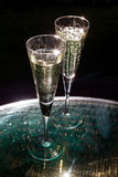 Two glasses of champagne. On the glass table on black background Royalty Free Stock Images