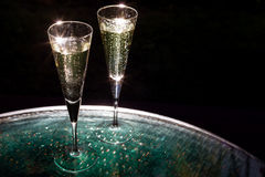 Two glasses of champagne. On the glass table on black background Stock Photos