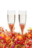 Two glasses of champagne and gold Christmas bauble Stock Photos
